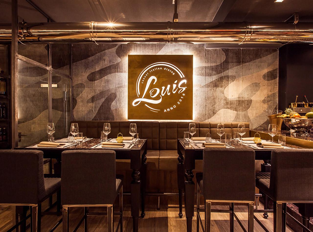 Beleuchtetes Schild mit Logo im Restaurant LOUIS 1